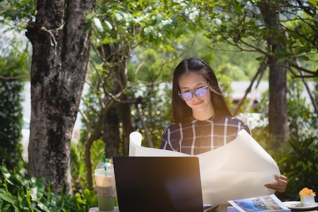 Werkneemster, student op zoek papier werken met ontspannen in de tuin op vakantie.