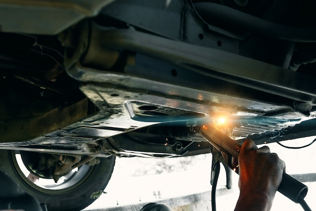 Werknemer auto carrosserie repareren, repareren service werknemer repareren beschadigde auto na crash op weg. werken met lasapparaat om metalen behuizing te bevestigen.
