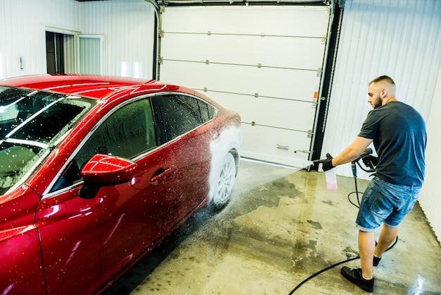 Werknemer auto met actief schuim op een wasstraat wassen.