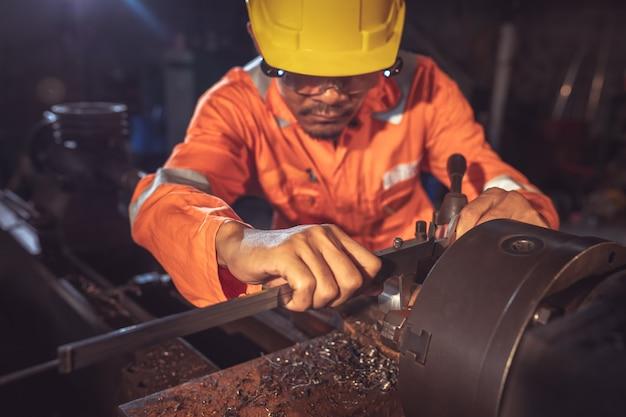 Werknemer behandelt metaal bij draaibank turner meet de afmetingen van het metalen werkstuk met een remklauw in uniform met veiligheid. werk aan een draaibank.