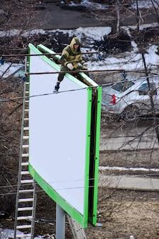 Werknemer bereidt billboard voor op het installeren van nieuwe advertenties. industriële klimmer die aan een ladder werkt - een reclamebanner plaatst.