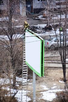 Werknemer bereidt billboard voor op het installeren van nieuwe advertenties.
