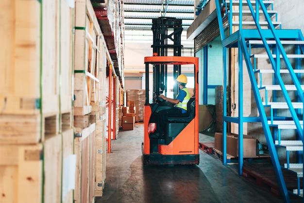 Werknemer bestuurder aziatische man in beschermende veiligheid jumpsuit uniform met gele veiligheidshelm bij magazijn heftruck lader werkt