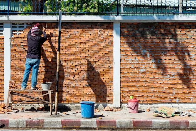 Werknemer bouwt een bakstenen muur