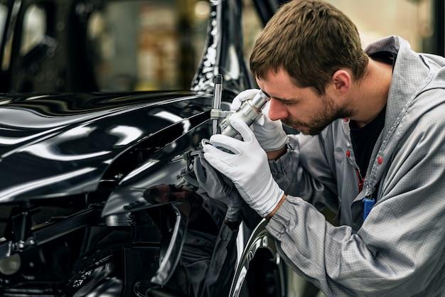 Werknemer carrosserie schilderwinkel controleert de kwaliteit met een microscoop