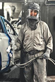Werknemer carrosserie schilderwinkel voert het schilderen van de interne elementen van de auto uit
