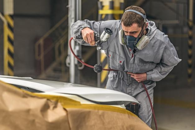 Werknemer carrosserie schilderwinkel voert schilderelement uit