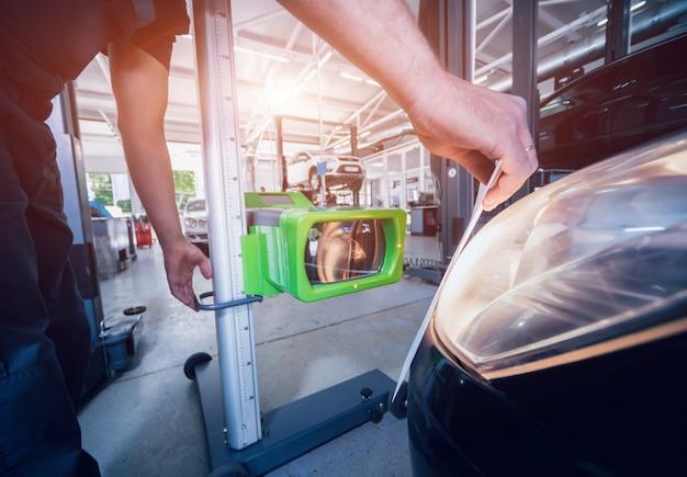 Werknemer controleert en past de koplampen van het verlichtingssysteem van een auto aan
