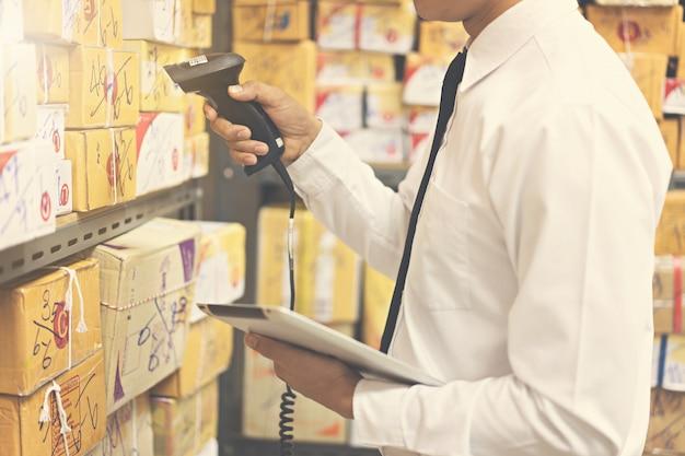 Werknemer controleren en scannen pakket in magazijn.