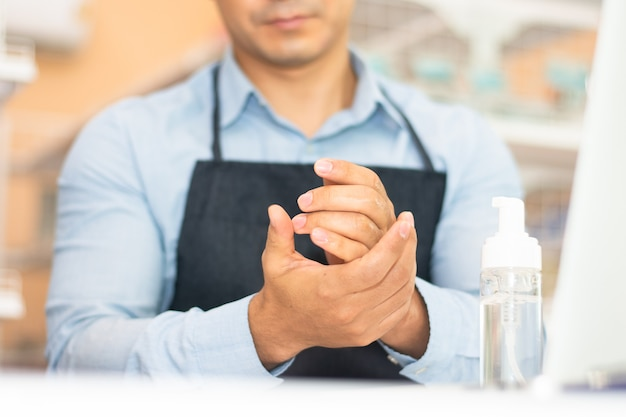 Werknemer die alcoholgel-reinigingshand gebruikt voor het werken in de coffeeshop