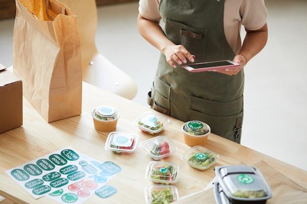 Werknemer die digitale tablet gebruikt tijdens het verpakken van bestellingen in de bezorgservice voor eten