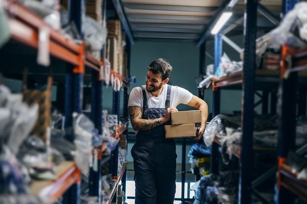 Werknemer die dozen verplaatst terwijl hij in opslag van import- en exportbedrijf loopt