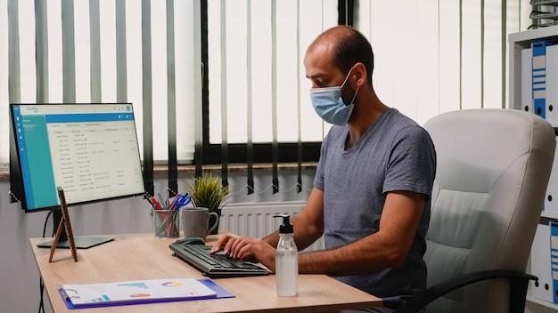 Werknemer die een beschermingsmasker draagt dat ontsmettingsgel gebruikt tijdens het coronavirus. ondernemer die werkt op een nieuwe normale kantoorwerkplek in een bedrijf dat handen schoonmaakt met antibacteriële alcohol tegen het coronavirus.