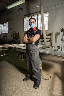 Werknemer die een masker en beschermende kleding draagt en naar de camera in een fabriek kijkt. long shot, full-body.