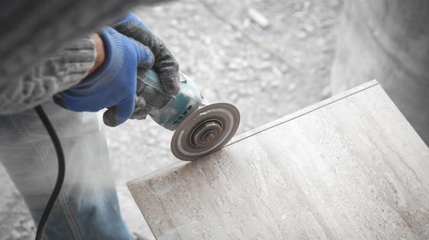 Werknemer die een tegel met een molen snijdt.