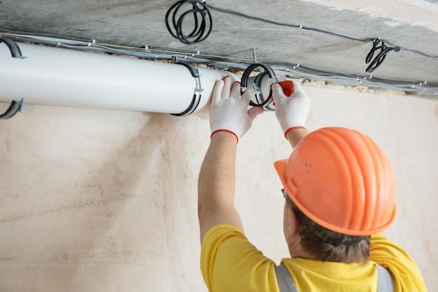Werknemer die een ventilatiesysteem in het appartement installeert