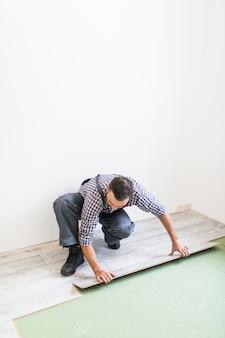 Werknemer die een vloer met laminaatvloerplaten verwerkt