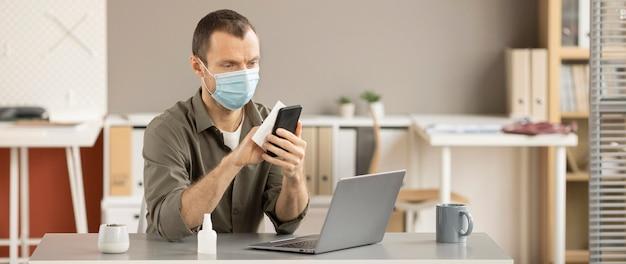 Werknemer die elektronisch apparaat desinfecteert