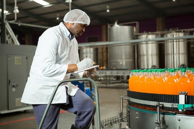 Werknemer die flessen in sap-fabriek controleert