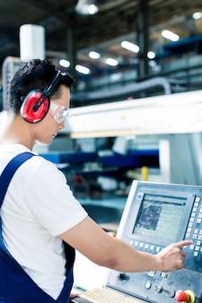 Werknemer die gegevens invoert in de cnc-machine op de fabrieksvloer om de productie op gang te krijgen