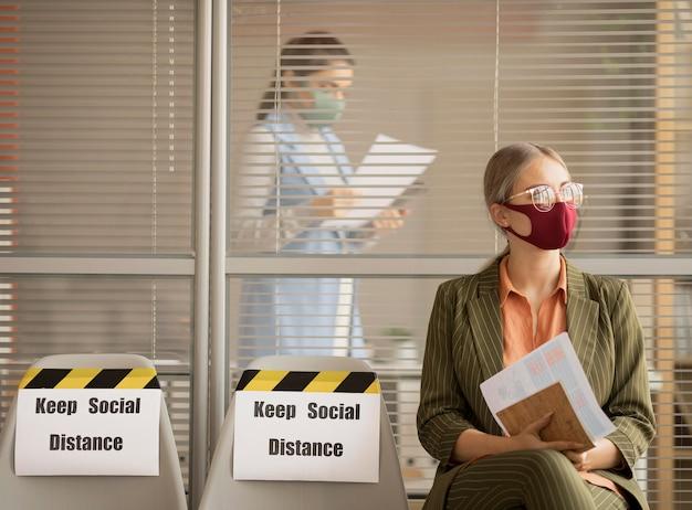 Werknemer die gezichtsmasker draagt dat een pauze neemt