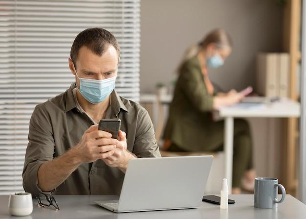 Werknemer die gezichtsmasker draagt op kantoor