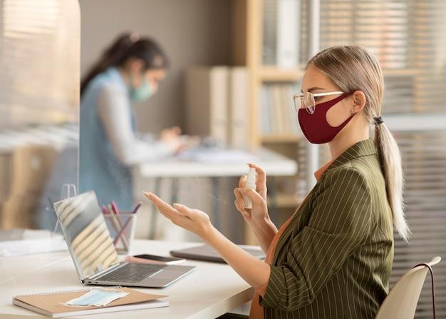 Werknemer die handen op het werk desinfecteert