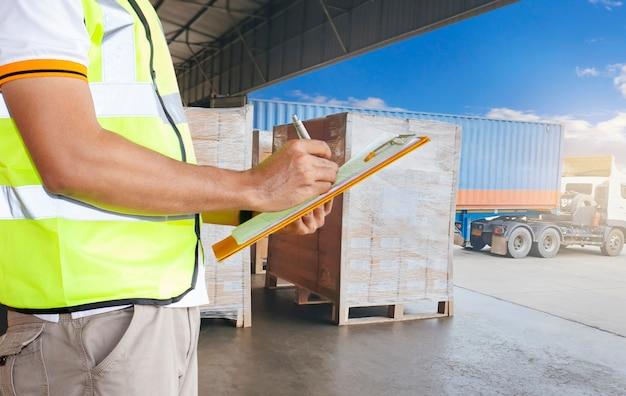 Werknemer die klembord houdt, is de verzending van de lading in de vrachtcontainer.