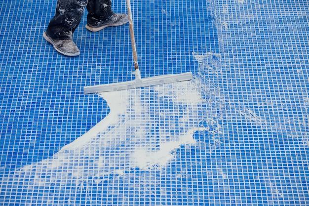 Werknemer die naden op de tegel in het zwembad bedekt. reparatiewerkzaamheden aan het zwembad