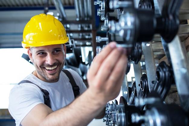 Werknemer die onderdelen voor de auto-industrie in de productielijn van de fabriek inspecteert