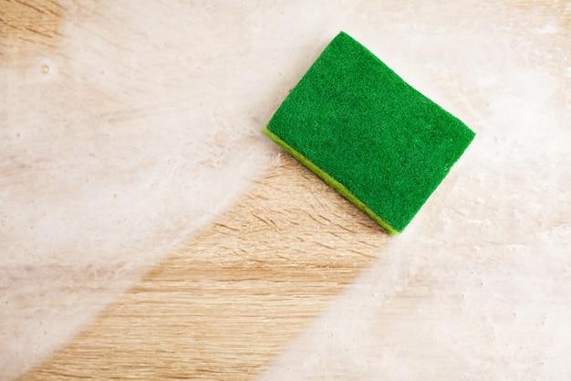 Werknemer die spons gebruikt voor het schoonmaken van houten tafel.