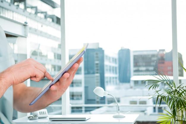 Werknemer die werkzaam zijn in zijn kantoor met een tablet