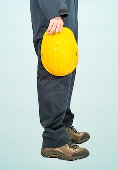 Werknemer die zich in blauwe overall bevindt die gele bouwvakker houdt die op blauwe achtergrond wordt geïsoleerd