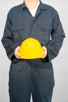 Werknemer die zich in blauwe overall bevindt die gele bouwvakker houdt die op grijze achtergrond wordt geïsoleerd