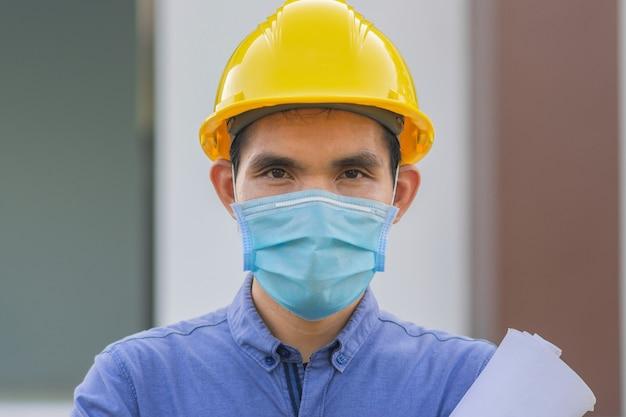 Werknemer draagt gezichtsmasker die op de bouwplaats werkt, man draagt masker beschermt coronavirus covid19
