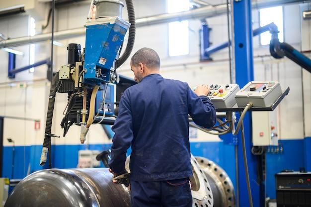 Werknemer een automatische lasmachine in een industriële installatie