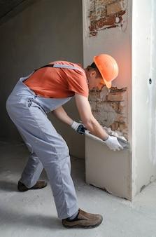 Werknemer een gipspleister op een bakstenen muur te zetten