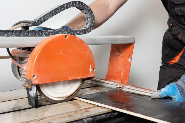 Werknemer een keramische tegel snijden op een natte snijder zag machine