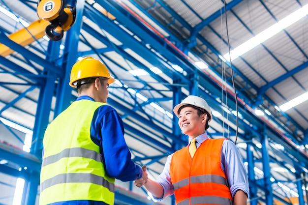 Werknemer en klant met overeenkomst in fabriek handen schudden
