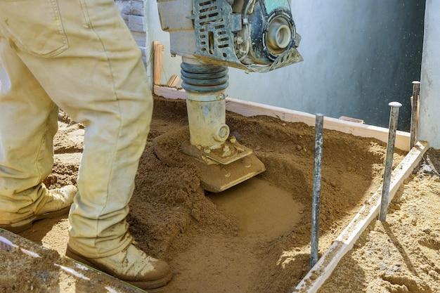 Werknemer gebruikt compactor trillend elektrisch gereedschap op de bodem op de bouw van de nieuwe stoep