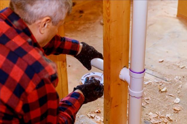Werknemer gebruikt lijm met fitting voor het installeren van de pvc-afvoerleiding in het werkgebied.