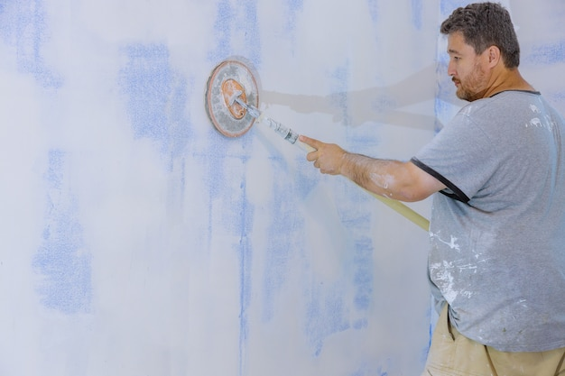 Werknemer gladmaken en afwerking muur met het schuren van de gipsplaat in gipsplaat