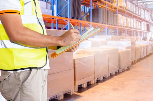 Werknemer hand houden klembord inventaris vrachtbeheer in opslag magazijn