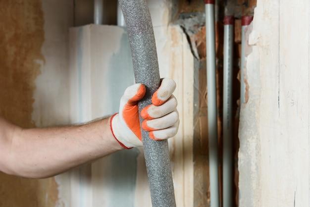 Werknemer hand met isolatie voor huis verwarmingsbuizen