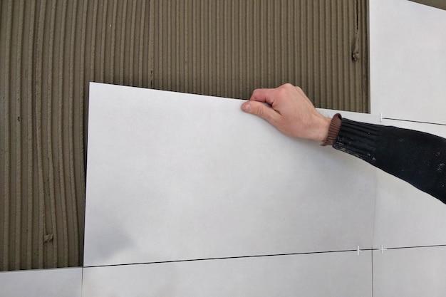 Werknemer handen zetten keramische tegels.