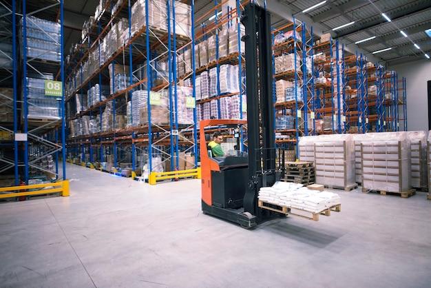 Werknemer heftruckmachine bedienen en goederen verplaatsen in groot magazijncentrum