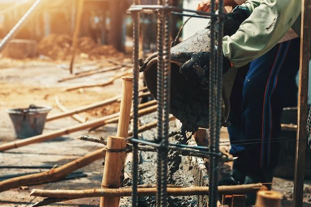 Werknemer het mengen giet bouwcement op vloer voor de bouw van huis