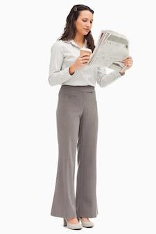 Werknemer het nieuws lezen met een kopje koffie in de hand