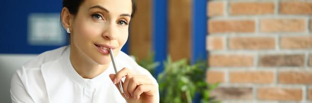Werknemer houdt een pen met haar lippen en denkt