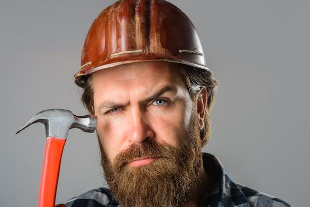 Werknemer houdt hamerbouwer vast met hamerportret van bebaarde werkman bouwtechnologie